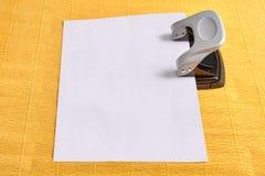 O perfurador é puncionado pela folha de papel vazia, fundo amarelo foto de stock royalty free