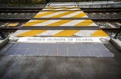 O perigo tem cuidado com o sinal dos trens pela trilha Imagens de Stock Royalty Free