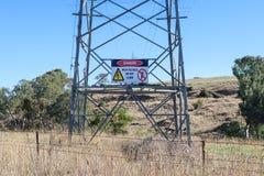 O perigo vermelho, preto e branco, não escala o sinal de aviso em uma torre da transmissão da eletricidade em Austrália rural imagens de stock
