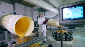 O perito fêmea está observando o processo de produzir batatas fritas video estoque