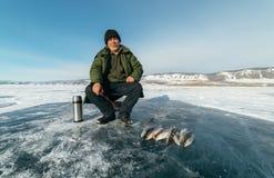 O pescador é um homem na pesca do inverno fotografia de stock royalty free