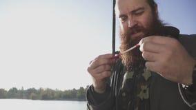 O pescador ajusta a vara de pesca Fisher farpado que prepara-se para pescar Pesca do rio Movimento lento vídeos de arquivo