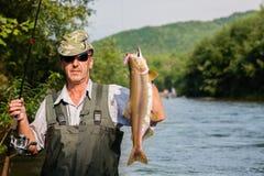 O pescador alegre mantém salmões cor-de-rosa travados Fotos de Stock Royalty Free