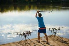 O pescador atrai peixes com isca no rio ou no lago imagem de stock royalty free