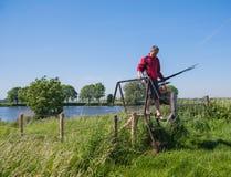 O pescador com haste de pesca retorna da pesca Fotografia de Stock Royalty Free