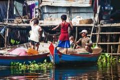 O pescador com suas crianças prepara o equipamento Imagens de Stock