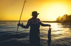 O pescador com uma vara de pesca em sua mão e em um peixe travado está na água contra um por do sol bonito Imagem de Stock Royalty Free