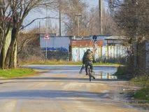 O pescador com uma vara de pesca monta em uma bicicleta imagem de stock
