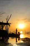 O pescador da silhueta está estando no barco de pesca Imagens de Stock Royalty Free