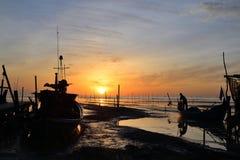 O pescador da silhueta está estando no barco de pesca Imagem de Stock