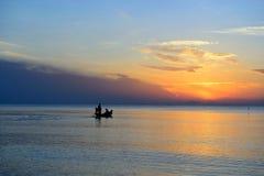 O pescador da silhueta está tomando o barco de pesca Foto de Stock