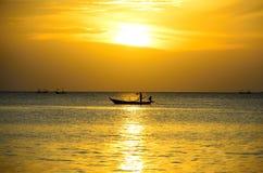 O pescador da silhueta está tomando o barco de pesca Foto de Stock Royalty Free