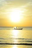 O pescador da silhueta está tomando o barco de pesca Fotografia de Stock