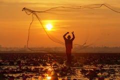 O pescador da silhueta que trabalha no barco no lago para o catchin imagem de stock