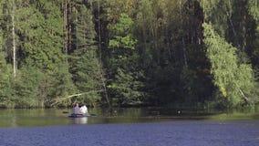O pescador dois no barco de borracha flutua o enfileiramento com os remos no rio O homem está pescando no lago no rio ensolarado  video estoque