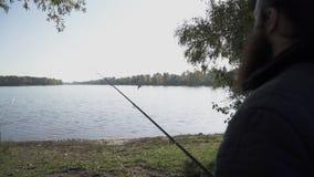 O pescador está com uma vara de pesca no banco de rio e olhares na água e em um voo do pássaro sobre a água lento filme