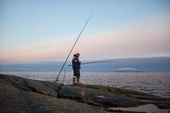 O pescador está em uma costa rochosa Foto de Stock