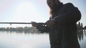 O pescador farpado ajusta a vara de pesca Fisher que prepara-se para pescar Pesca no rio video estoque