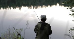 O pescador joga uma vara de pesca no banco de rio vídeos de arquivo
