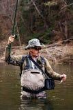 O pescador mantém o timalo travado no rio limpo imagem de stock