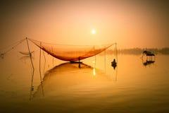 O pescador não identificado verifica suas redes no amanhecer no rio em Hoian, Vietname imagens de stock