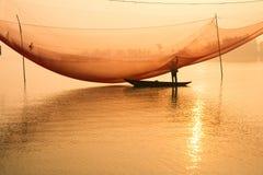O pescador não identificado verifica suas redes no amanhecer no rio em Hoian, Vietname Fotos de Stock Royalty Free