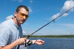 O pescador nos óculos de sol mantém-se girar com quinquilharias contra um céu azul foto de stock royalty free