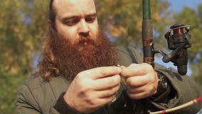 O pescador põe um sem-fim sobre o gancho e pontos sobre ele Retrato do homem adulto com a barba que põe o bailt sobre o gancho pe video estoque
