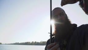 O pescador põe um sem-fim sobre o gancho e pontos sobre ele Retrato do homem adulto com barba que está pescando Pesca do rio video estoque