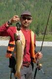 O pescador pesa uma truta asiática bonita no verão Fotos de Stock Royalty Free