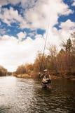 O pescador puxa a truta no rio Fotos de Stock