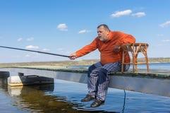 O pescador que senta-se em um cais com haste e apronta-se para travar peixes Imagem de Stock Royalty Free