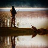 O pescador solitário trava peixes imagens de stock