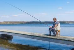 O pescador superior que senta-se no tamborete de vime em um cais com haste e apronta-se para travar peixes Imagem de Stock
