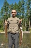 O pescador sustenta dois grandes peixes Fotos de Stock