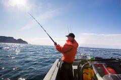 O pescador trava o meio do atleta do mar com barcos foto de stock royalty free