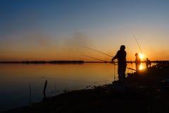 O pescador trava peixes girando no lago no por do sol Foto de Stock