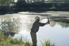 O pescador trava peixes para girar Lambe a isca fotos de stock