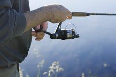 O pescador trava peixes para girar Puxa a linha de pesca com uma girar-roda fotografia de stock