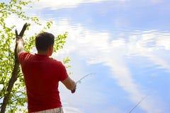 O pescador trava um peixe Mãos de um pescador com um close up disponivel da haste de giro Carretel da pesca da rotação imagens de stock