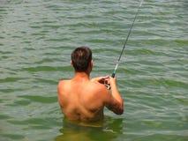 O pescador trava um peixe na água Fotos de Stock Royalty Free