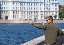 O pescador trava um peixe no rio de Neva Fotos de Stock
