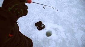 O pescador trava a vara de pique na obscuridade com um receptor acústico do inverno video estoque