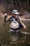 O pescador travou o timalo e puxa-o fora do rio fotos de stock
