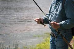 O pescador travou um peixe pequeno Foto de Stock Royalty Free