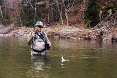 O pescador travou um timalo em um rio da montanha Foto de Stock Royalty Free