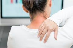 O pescoço e o ombro das jovens mulheres causam dor a ferimento com destaques vermelhos na área da dor, nos cuidados médicos e no  fotografia de stock
