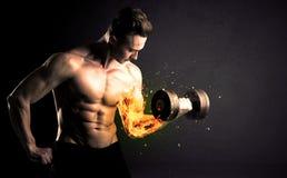 O peso de levantamento do atleta do halterofilista com fogo explode o conceito do braço imagem de stock