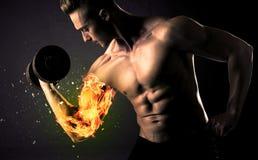 O peso de levantamento do atleta do halterofilista com fogo explode o conceito do braço fotos de stock royalty free
