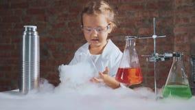 O pesquisador bonito da criança está conduzindo uma experiência com nitrogênio líquido video estoque